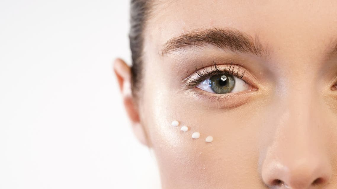 Close up of the face of a beautiful woman with perfect skin thanks to creams to keep young and cream contour anti-aging and wrinkle eyes. stock photo