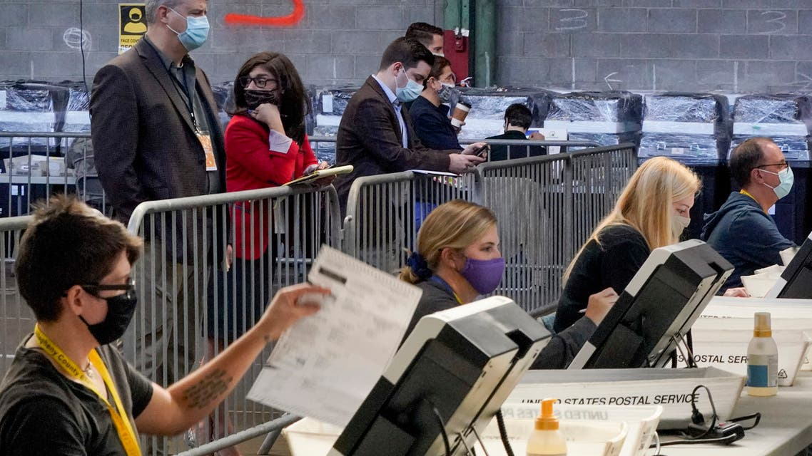 Election observers stand behind a barrier and watch as election office workers process ballots as counting continues from the general election at the Allegheny County elections returns warehouse in Pittsburgh, Friday, Nov. 6, 2020. (AP Photo/Gene J. Puskar)