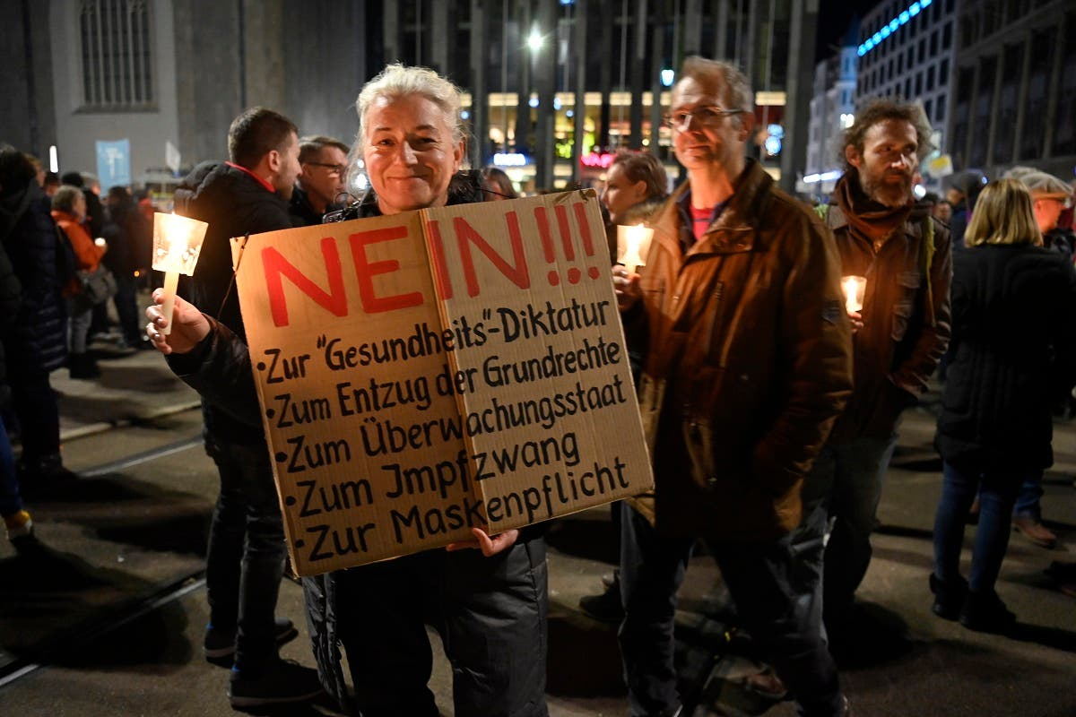 A participant holds up a placard rejecting the government's measures to curb the coronavirus during a protest in Leipzig, eastern Germany, on November 7, 2020. (AFP)