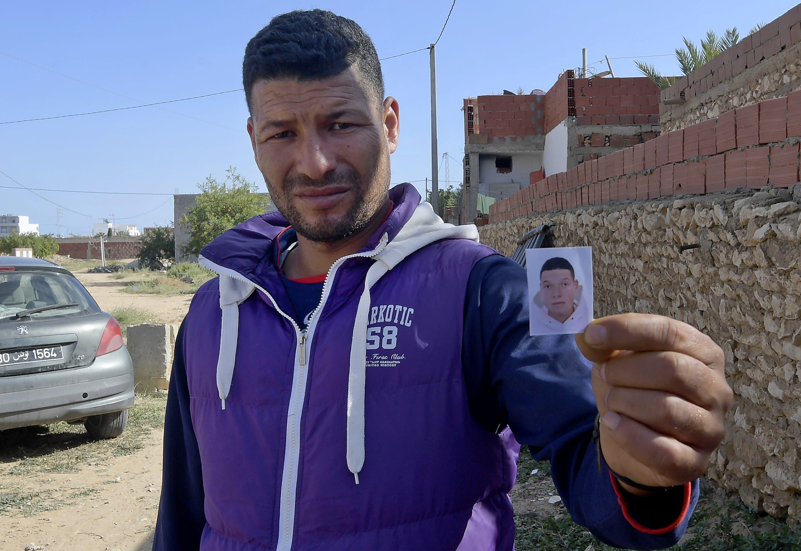ياسين، شقيق ابراهيم عويساوي منفذ هجوم نيس، يحمل صورته قرب منزل العائلة في صفاقس