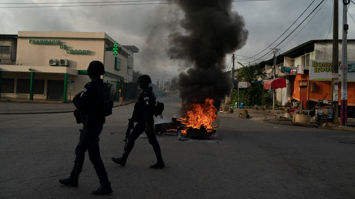 Policemen walk past a burning barricade during a protest after the security forces blocked the access to the house of the former president Henri Konan Bedie, in Abidjan, Ivory Coast, Tuesday, Nov. 3, 2020. (AP)