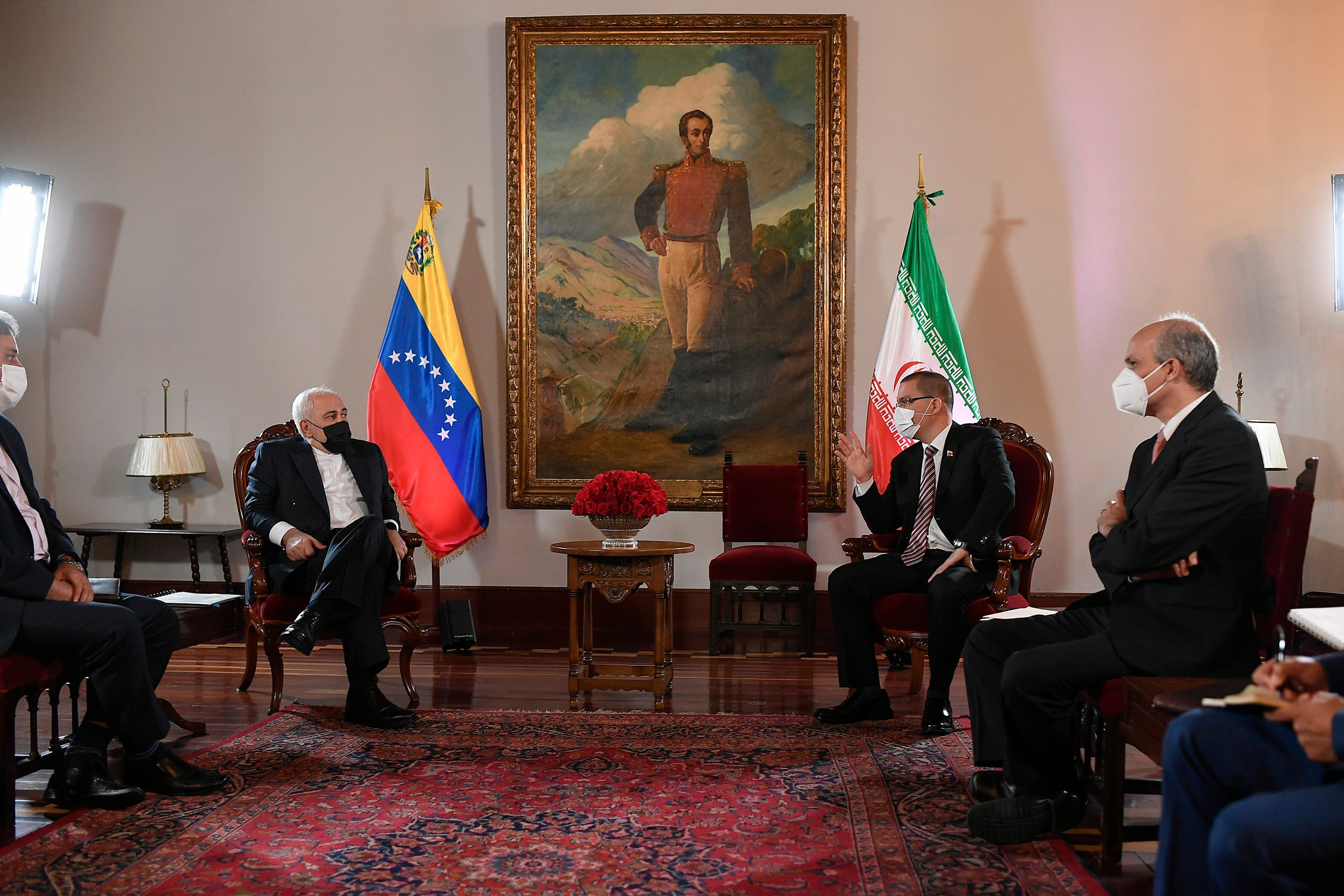 Iran's Foreign Minister Mohammad Javad Zarif, left, sits with Venezuela's Foreign Minister Jorge Arreaza, second from right, during a photo opportunity at the Foreign Ministry where a painting of Venezuela's independence hero Simon Bolivar hangs in Caracas, Venezuela, Thursday, Nov. 5, 2020, amid the COVID-19 pandemic. (AP Photo/Matias Delacroix)