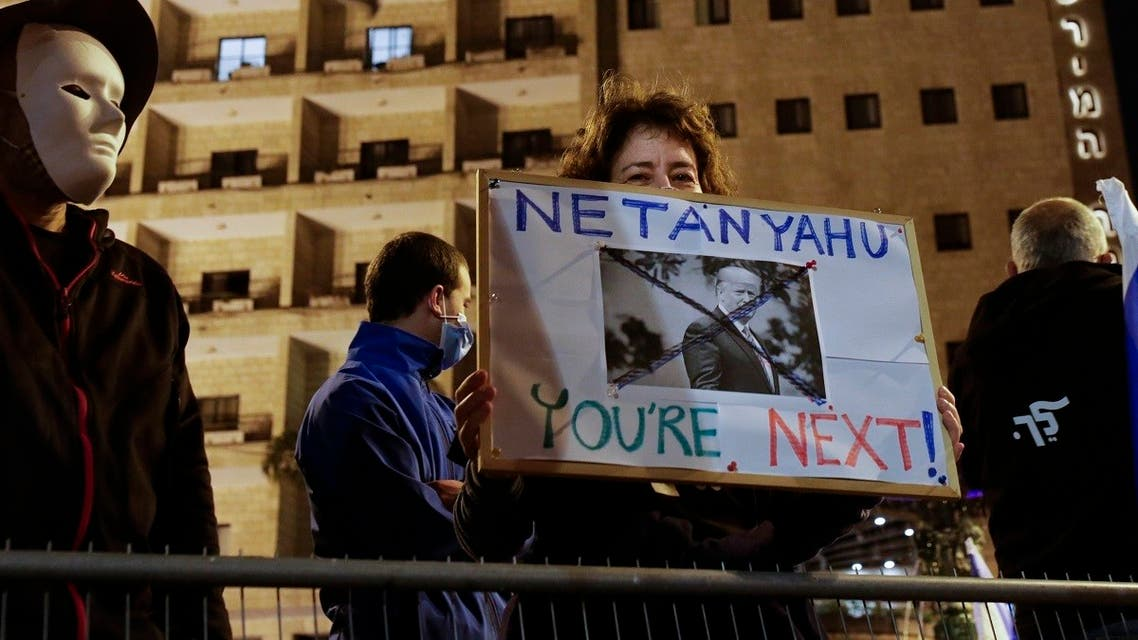 An Israeli protester holds a sign with a photo of President Trump, calling for the ouster of PM Netanyahu, shortly after results of the US presidential election were announced, during a protest against Netanyahu in Jerusalem, Nov. 7, 2020. (AP/Maya Alleruzzo)