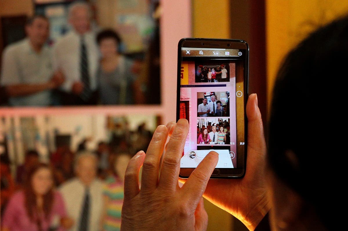 A woman takes a smartphone photo of Joe Biden's pictures on display at a restaurant where he visited in 2011, in Beijing, Sunday, Nov. 8, 2020. (AP/Andy Wong)