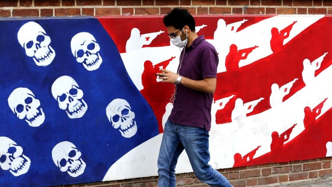An Iranian man walks past a mural painted on the outer walls of the former US embassy in the Iranian capital Tehran, on November 4, 2020. (AFP)