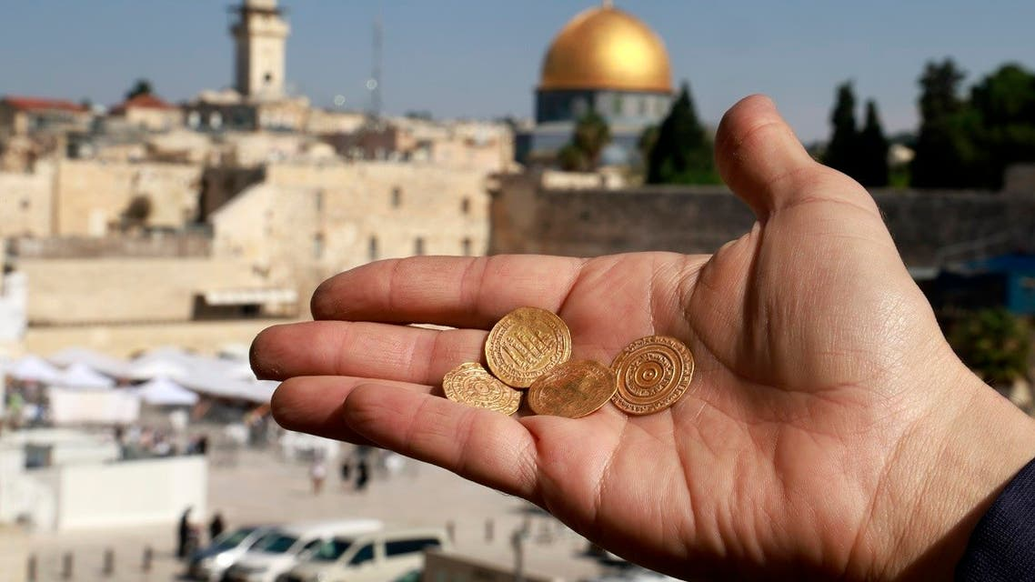 Archaeologist shows four pure gold coins discovered in a small pottery jug at the archaeological rescue excavation in the Old City of Jerusalem, on November 9, 2020. (Menahem Kahana/AFP)