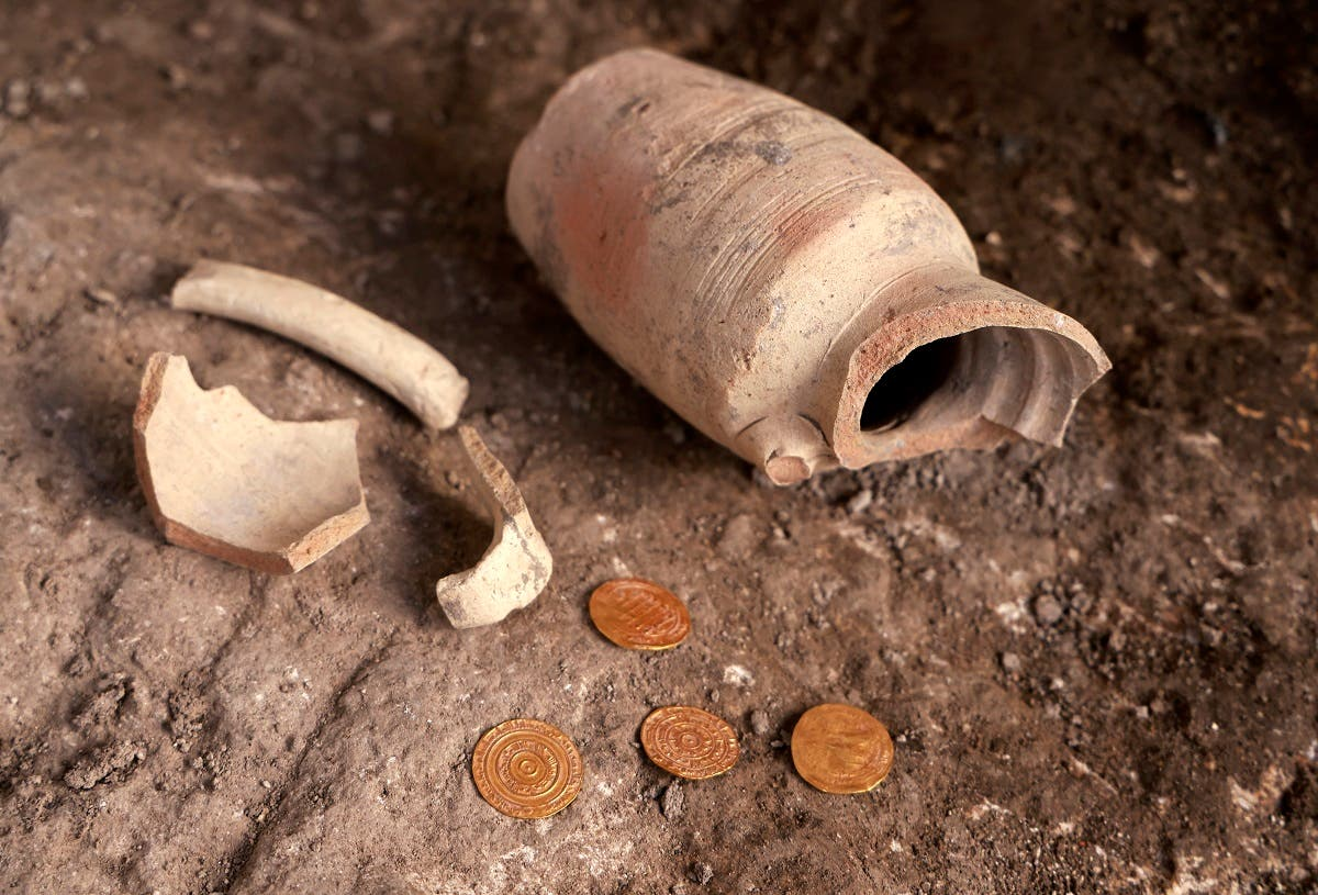 A small pottery jug with four pure gold coins found inside it by the Israel Antiquities Authority are displayed at the archaeological rescue excavation site in the Old City of Jerusalem, on November 9, 2020. (Menahem Kahana/AFP)