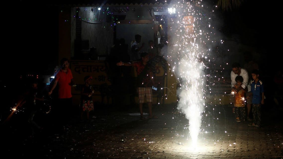 People watch as firecrackers burn on a street during Diwali, the Hindu festival of lights, in Mumbai, India. (Reuters)
