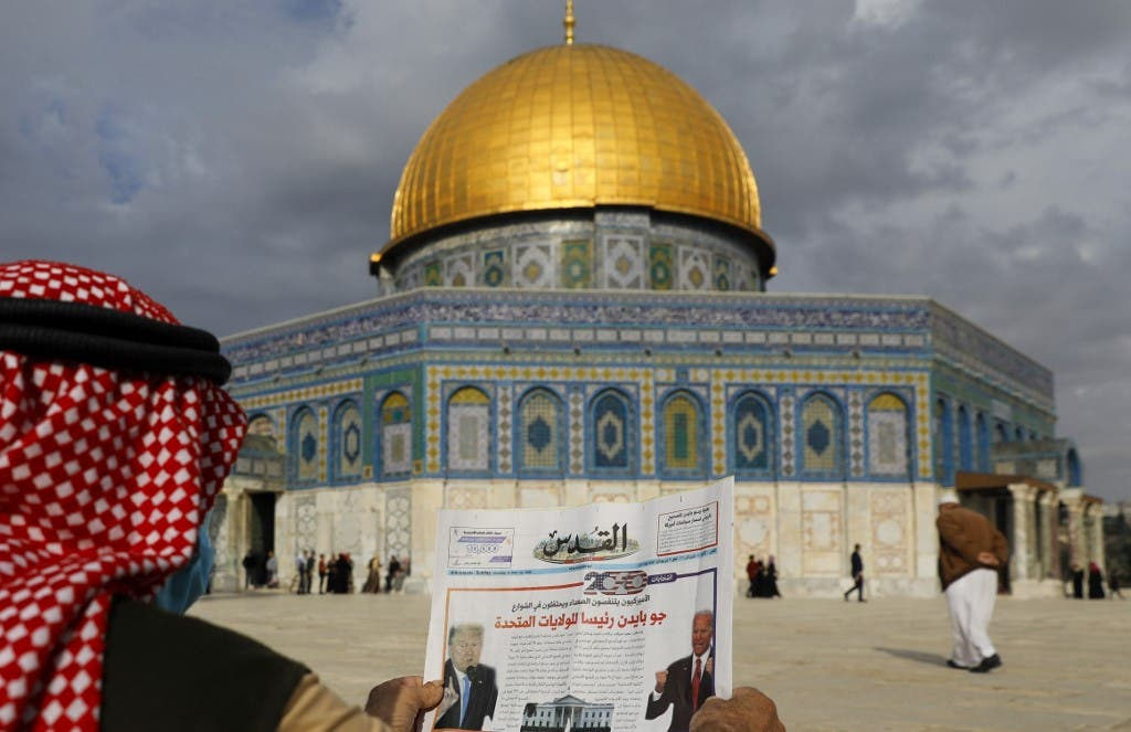 "A Palestinian man reads the front page of Al-Quds newspaper, headlined in Arabic ""Joe Biden the new US President"" in front of the Dome of the Rock in the al-Aqsa mosque compound in East Jerusalem on November 8, 2020. (AFP)"