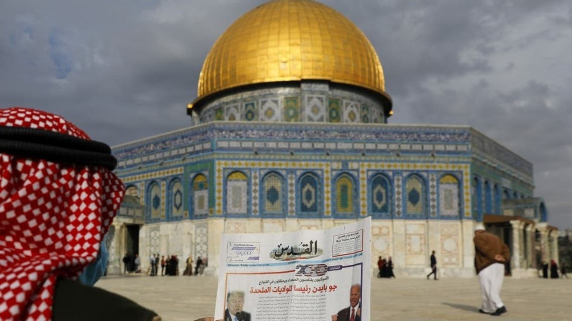 A Palestinian man reads the front page of Al-Quds newspaper, headlined in Arabic Joe Biden the new US President in front of the Dome of the Rock in the al-Aqsa mosque compound, Islam's third holiest site, in the old city of Jerusalem on November 8, 2020. (AFP)