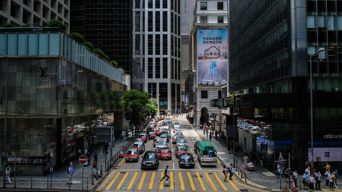 A pedestrian (C) runs across a pedestrian crossing between commercial buildings in the Central district of Hong Kong on July 16, 2020. Beijing's tough new security law and President Donald Trump's order to rescind special trading privileges have blunted Hong Kong's competitive edge and risk turning the finance hub into just another Chinese city, analysts warn.