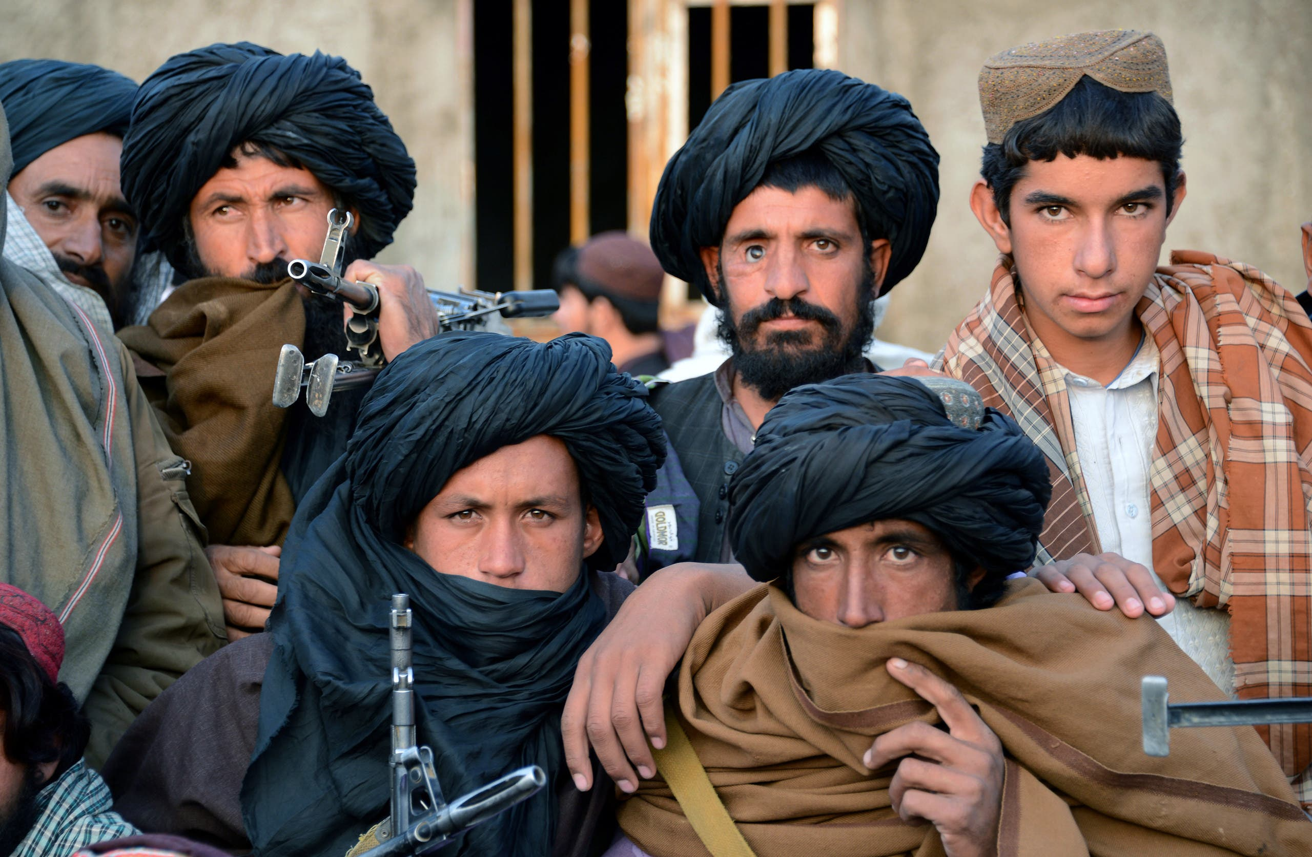 In this photograph taken on November 3, 2015, Afghan Taliban fighters look on as they listen to Mullah Mohammad Rasool Akhund (unseen), the newly appointed leader of a breakaway faction of the Taliban, at Bakwah in the western province of Farah. (AFP)