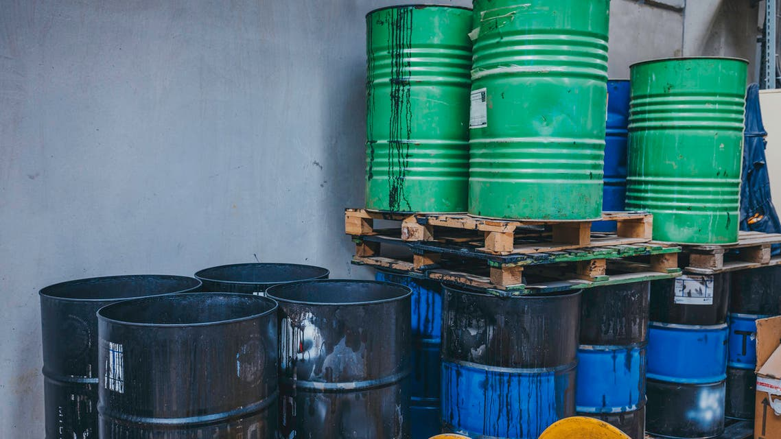 Old iron barrels in warehouse stock photo Old chemical barrels. Blue and orange oil drum. Steel oil tank. Toxic waste warehouse. Hazard chemical barrel with warning label. Industrial waste in metal drum. Hazard waste storage in factory.