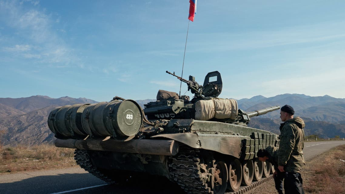 Service members of the Russian peacekeeping troops stand next to a tank near the border with Armenia in the region of Nagorno-Karabakh, November 10, 2020. (Reuters)