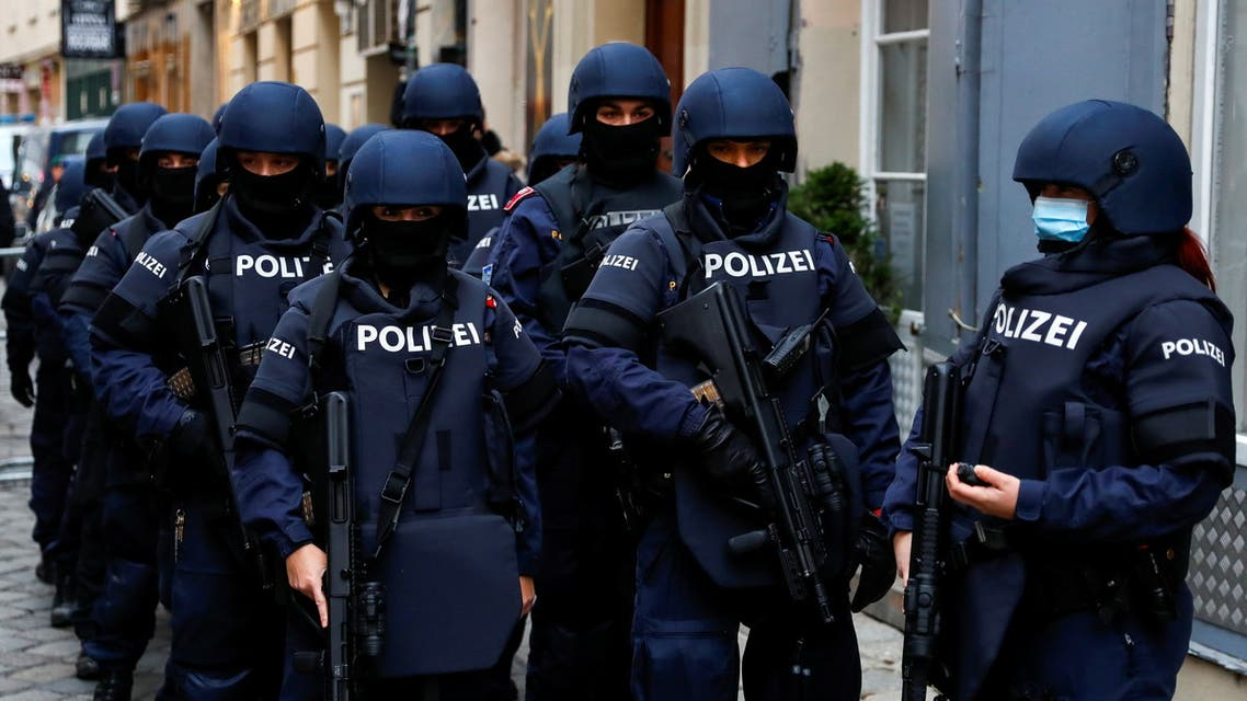 Police officers stand guard during a ceremony at the site of a gun attack in Vienna, Austria, November 9, 2020. REUTERS/Leonhard Foeger