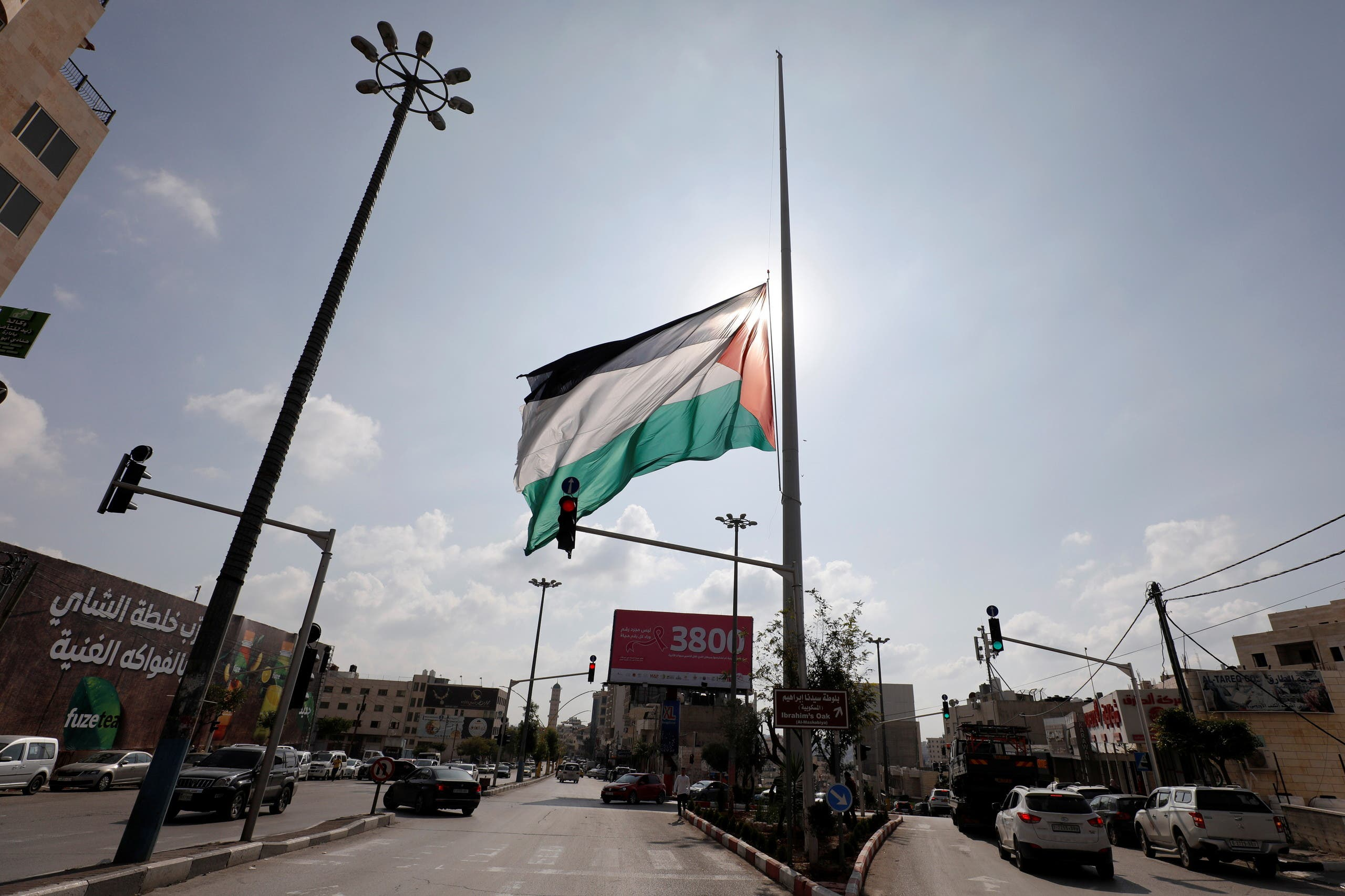 A Palestinian flag flies at half-mast after President Mahmoud Abbas declared a three-day mourning period for Saeb Erekat, the chief Palestinian negotiator who died after contracting the coronavirus disease (COVID-19). (Reuters)