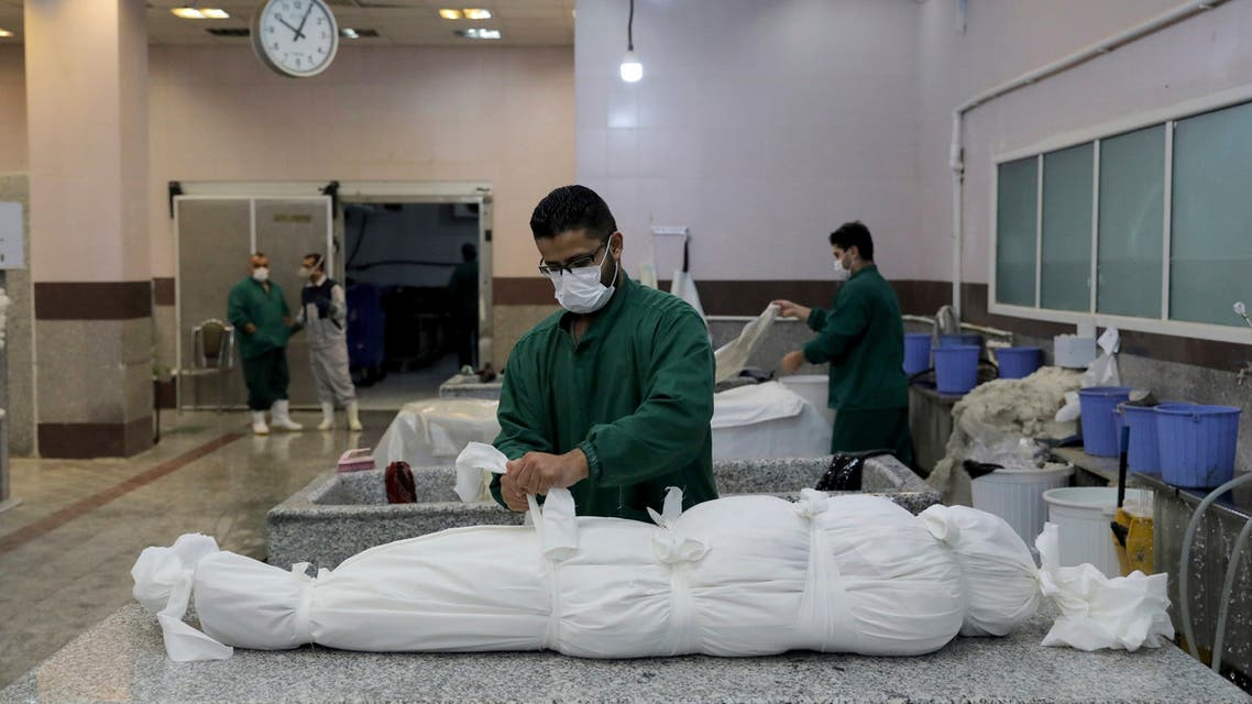 An Iranian cemetery worker prepares the body of a man who died from COVID-19, in a morgue at the Behesht-e-Zahra cemetery on the outskirts of the Iranian capital, Tehran, Iran, Sunday, Nov. 1, 2020. The cemetery is struggling to keep up with the coronavirus pandemic ravaging Iran, with double the usual number of bodies arriving each day and grave diggers excavating thousands of new plots. (AP Photo/Ebrahim Noroozi)