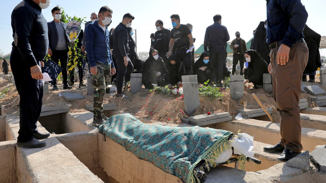 Mourners attend the funeral of a person who died from COVID-19 at the Behesht-e-Zahra cemetery on the outskirts of Tehran, Iran, Sunday, Nov. 1, 2020. The cemetery is struggling to keep up with the coronavirus pandemic ravaging Iran, with double the usual number of bodies arriving each day and grave diggers excavating thousands of new plots. (AP Photo/Ebrahim Noroozi)