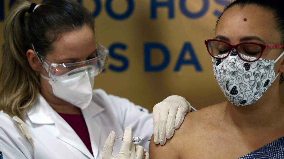 FILE PHOTO: Nurse Isabelli Guasso administers China's Sinovac vaccine, a potential vaccine for the coronavirus disease (COVID-19), to volunteer and nurse Fabiana Souza, at the Sao Lucas Hospital of the Pontifical Catholic University of Rio Grande do Sul (PUCRS), in Porto Alegre, Brazil August 8, 2020. REUTERS/Diego Vara/File Photo