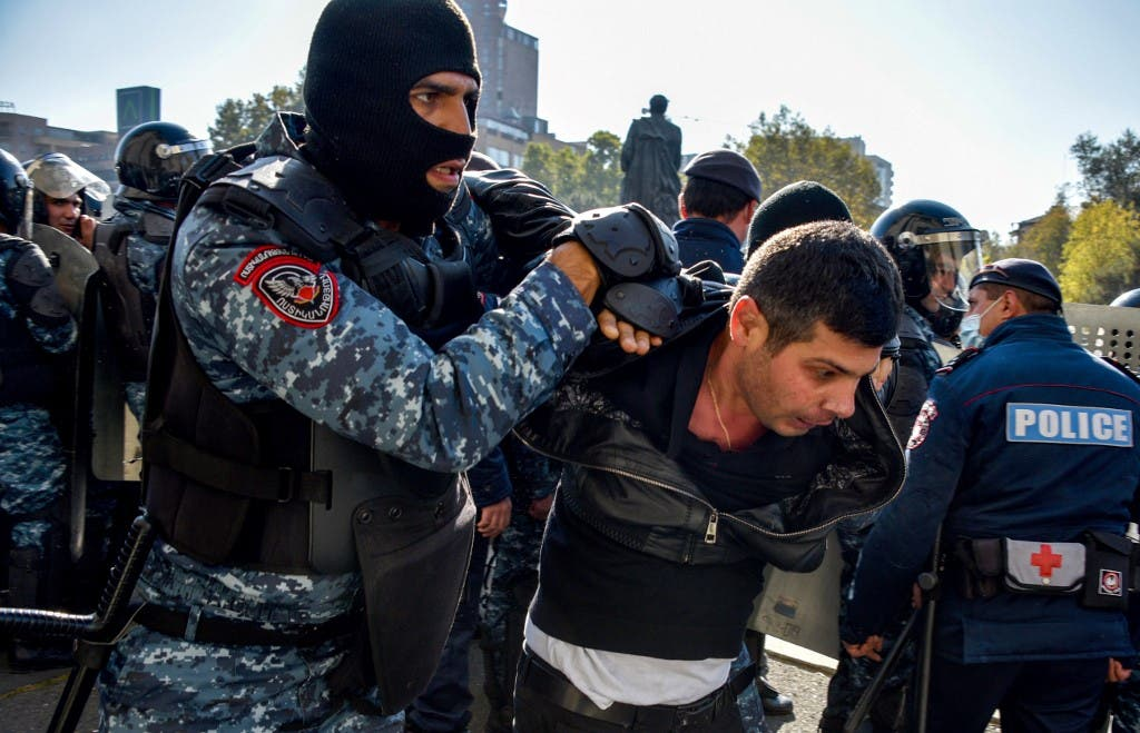 Armenian police officers detain a protestor during a rally against the country's agreement to end fighting with Azerbaijan over the disputed Nagorno-Karabakh region outside the government headquarters in Yerevan on November 11, 2020. (AFP)