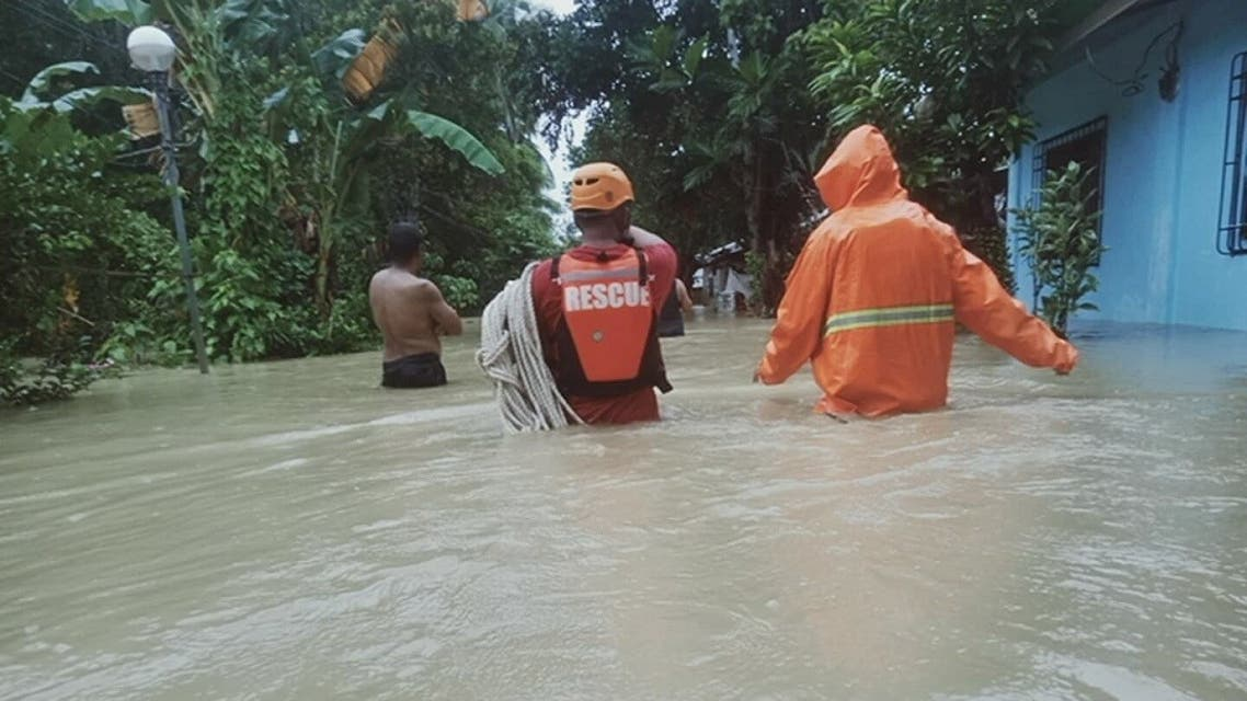 Members of a rescue team walk in floodwater in Caluag Town, Quezon province, Philippines, on October 21, 2020, in this picture obtained from social media. Municipal Disaster Risk Reduction and Management Office – Caluag. (Reuters)