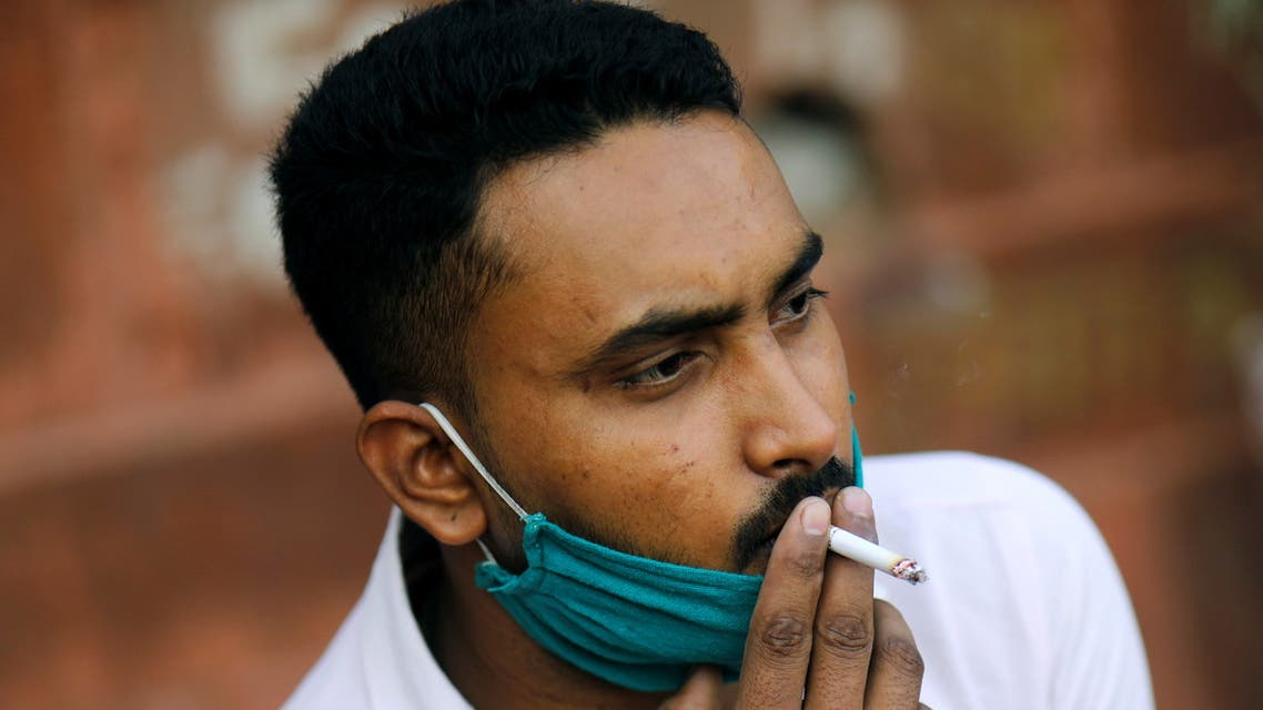 A man wearing a protective face mask smokes a cigarette amidst the spread of the coronavirus disease (COVID-19) in the old quarters of Delhi, India, October 20, 2020. (Reuters)