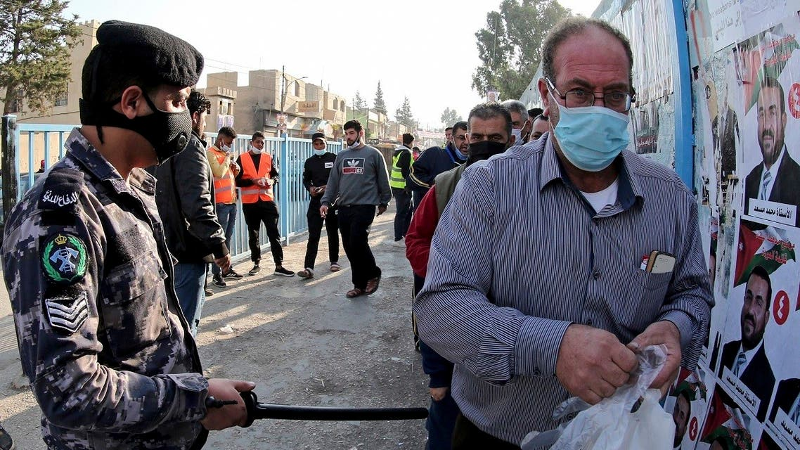 A man is checked with a metal detector outside a polling station as Jordanians begin voting in a parliamentary election overshadowed by the coronavirus pandemic, in Amman, Nov. 10, 2020. (AP)