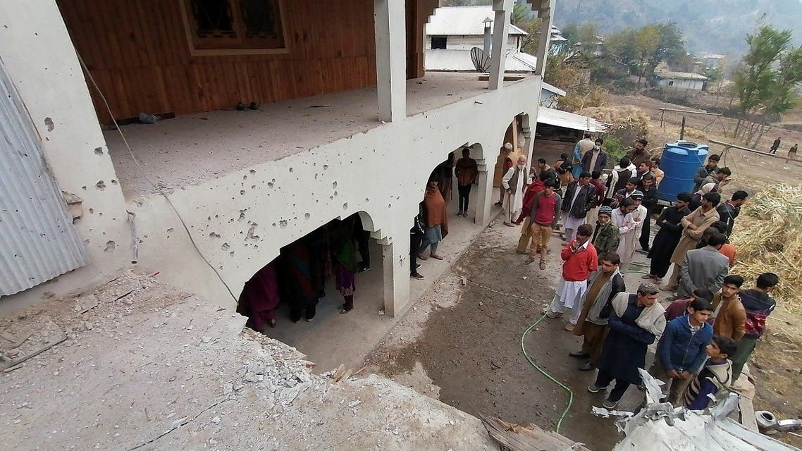 Locals gather near a house, which was damaged, according to them, by cross-border shelling, in Neelum Valley, in Pakistan-administrated Kashmir, on November 13, 2020. (Reuters)