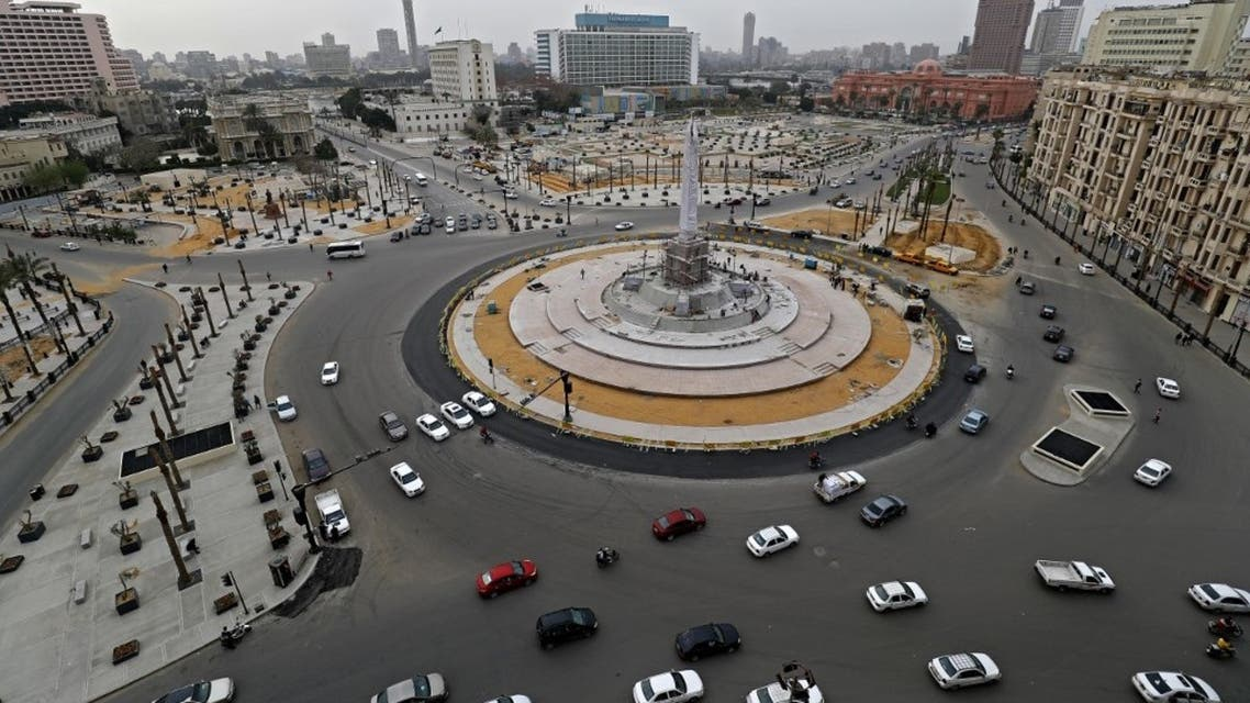Cars drive in the Egyptian capital Cairo's Tahrir square, shortly before the first day of a two-weeks night-time curfew imposed by the authorities to contain the spread of the coronavirus began on March 25, 2020. (AFP)