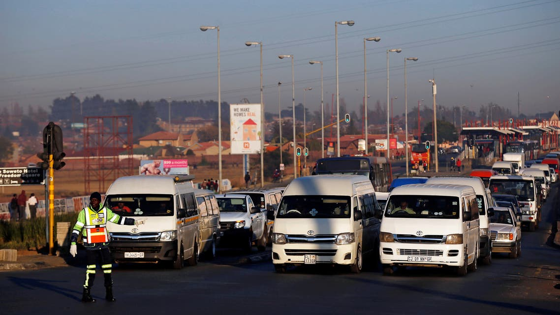 A traffic controller gestures in front of minibus taxis as they transport commuters to work, in Soweto, Johannesburg, South Africa June 15, 2017. (Reuters)