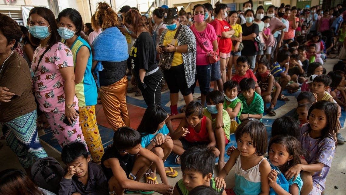 Residents affected by the onslaught of Typhoon Vamco queue for food in an evacuation center, in Rodriguez, Rizal province, Philippines, November 14, 2020. (Reuters)