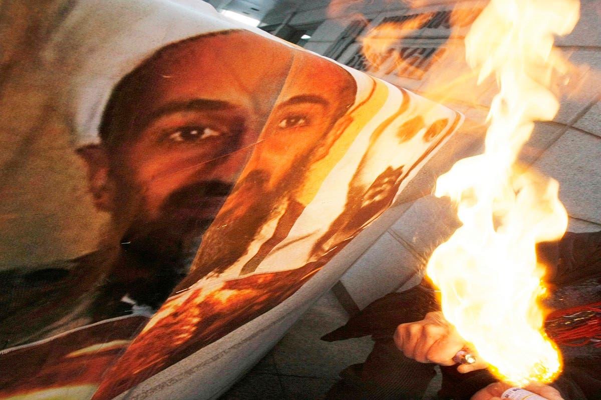 A man burns a portrait of al-Qaeda leader Osama bin Laden, left, and Jordanian-born terrorist mastermind Abu Musab Al-Zarqawi, Jan. 3, 2010. (AP)
