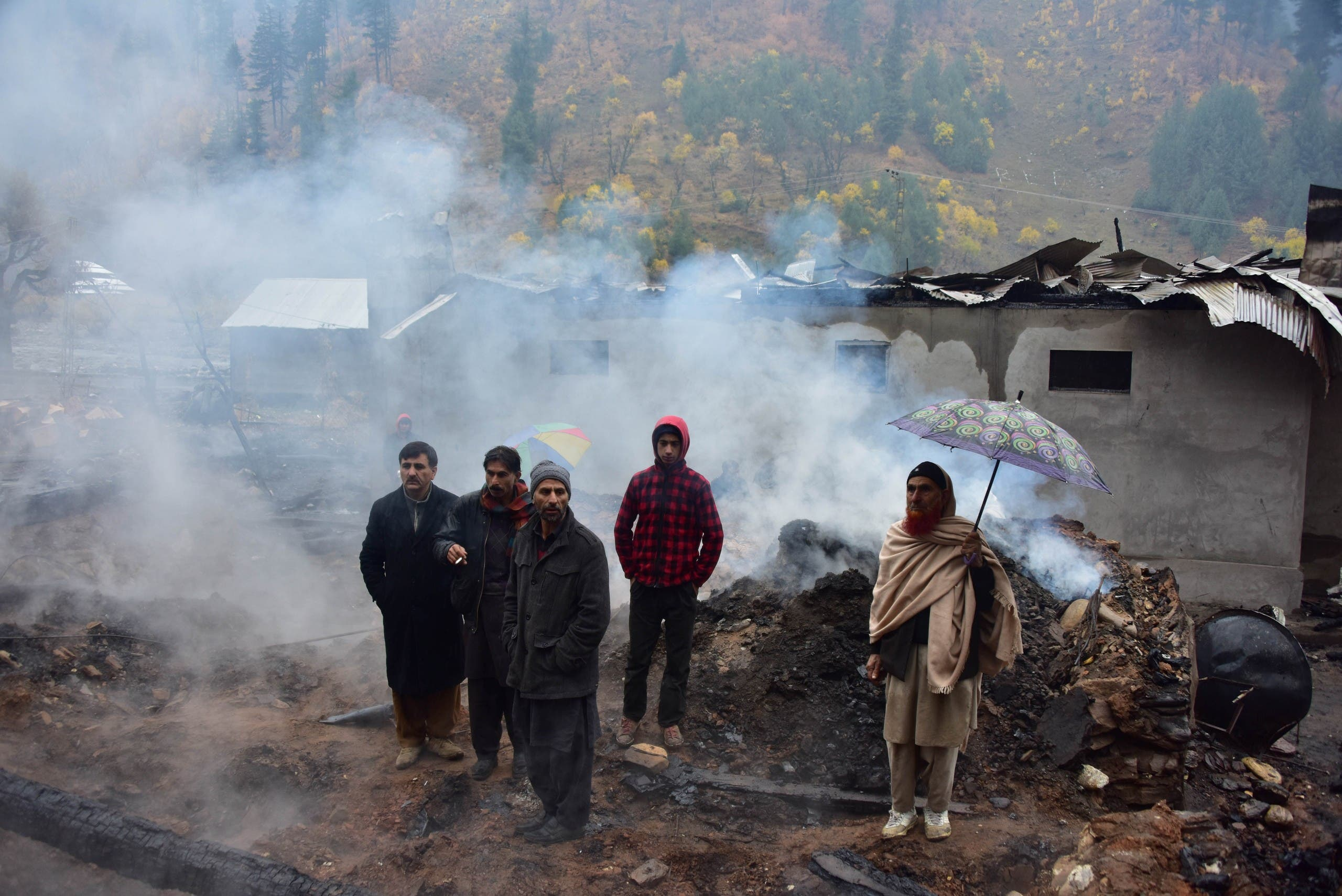 سكان من كشمير يقفون أمام منازل مدمرة بسبب القصف، الجمعة