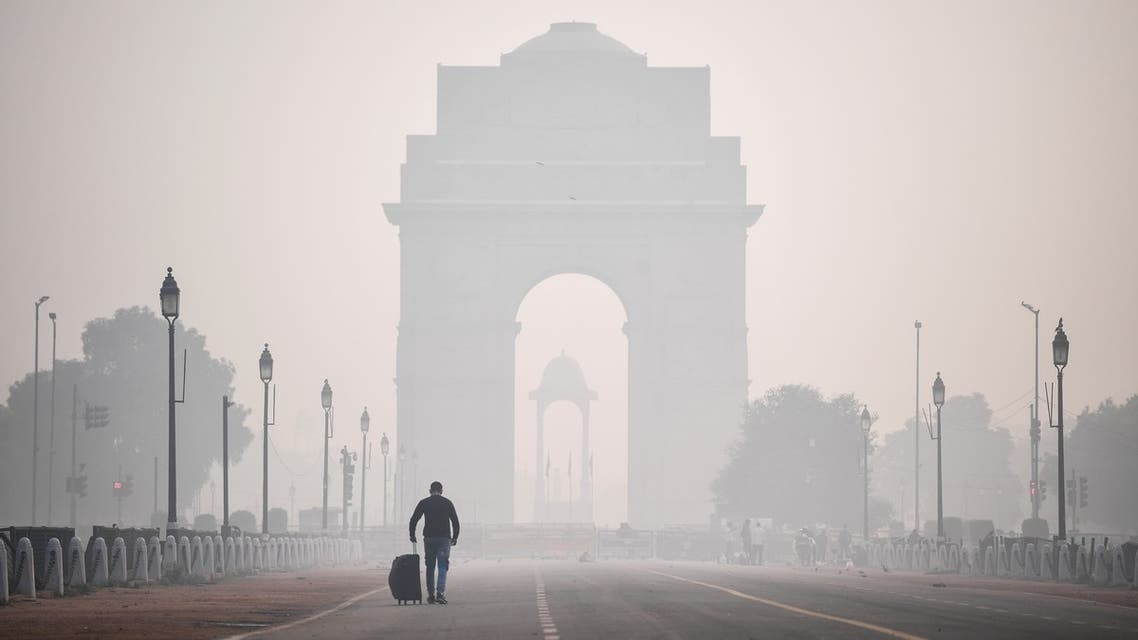 A man walks along the Rajpath street near India Gate amid smoggy conditions a day after Diwali, the Hindu festival of lights, in New Delhi on November 15, 2020.