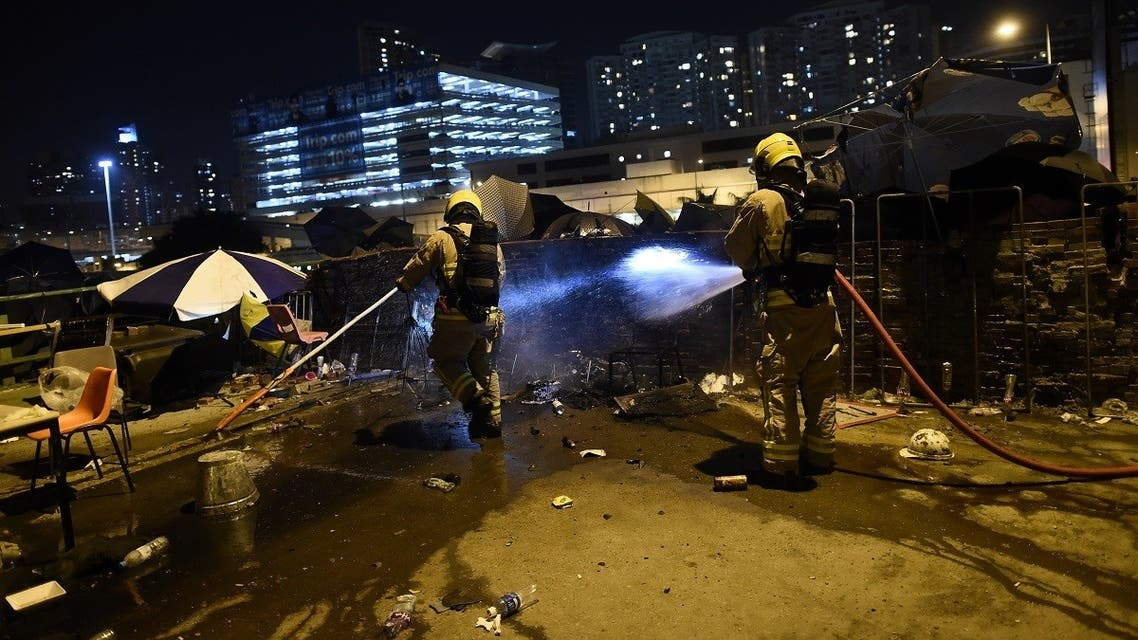 Fire fighters extinguish fire on the barricades in the main road next to the Polytechnic University of Hong Kong in Hung Hom district of Hong Kong on November 16, 2019. (Ye Aung Thu/AFP)