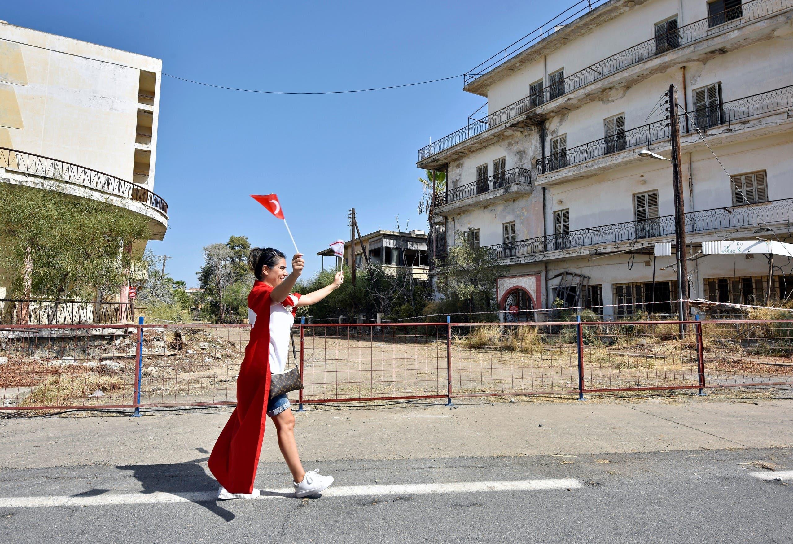 شابة ترفع علمَيْ تركيا وجمهورية قبرص التركية في منتجع فاروشا
