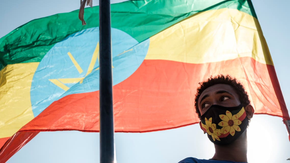 A youngster stands below an Ethiopian national flag during a blood donation rally organised by the city administration of Addis Ababa, in Addis Ababa, on November 12, 2020. Hundreds of Ethiopians gathered in the capital on November 12, 2020, to donate blood for troops fighting in the northern Tigray region, as officials tried to rally support for a conflict Prime Minister Abiy Ahmed said was going his way.