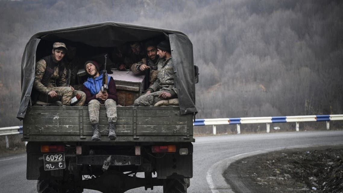 Armenian soldiers sit in the back of a truck as they drive along a road outside Kalbadjar on November 15, 2020. (AFP)