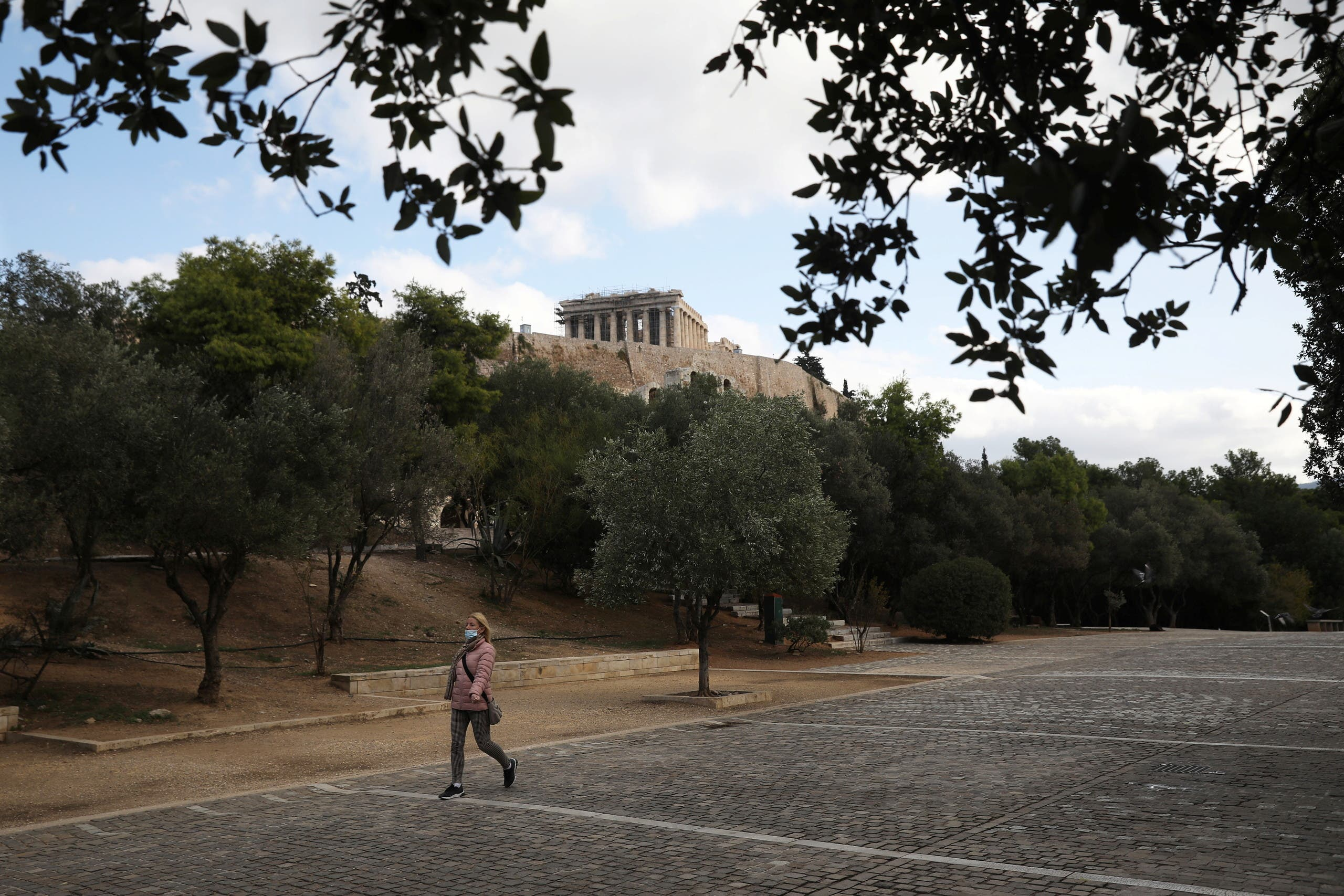 A woman makes her way, as the Parthenon Temple is seen atop the ancient Acropolis in Athens. (Reuters)