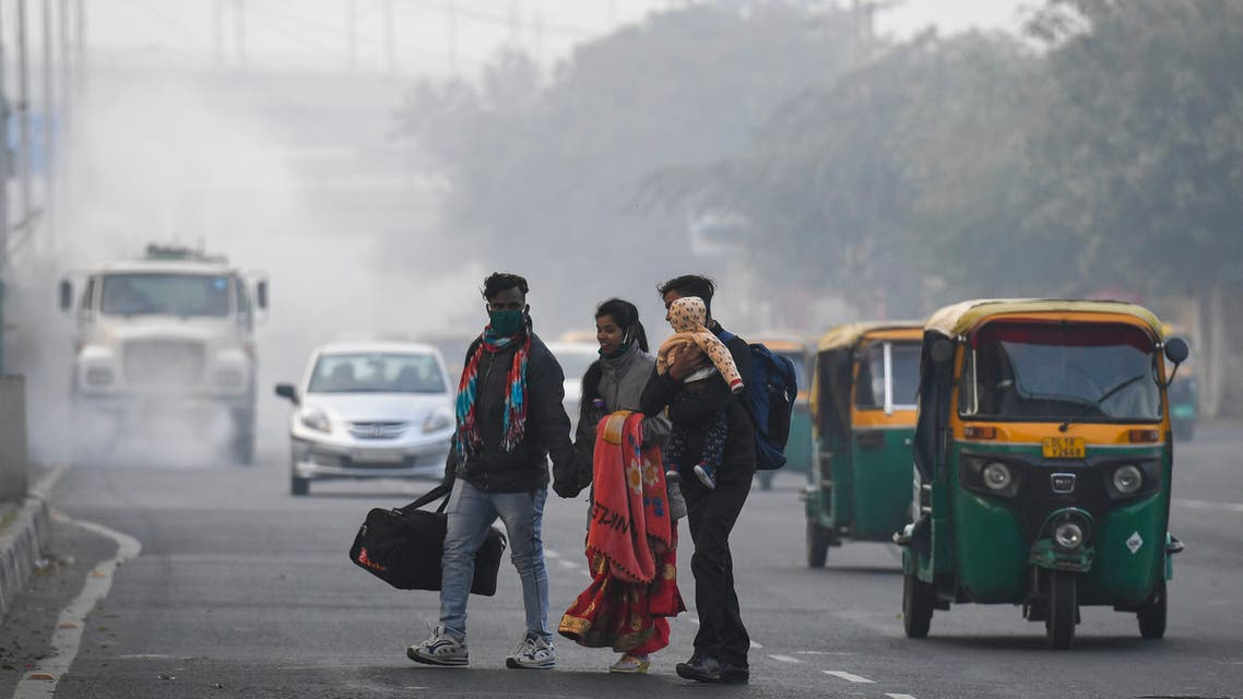 People cross a street as motorists drive past amid smoggy conditions in New Delhi on November 15, 2020.