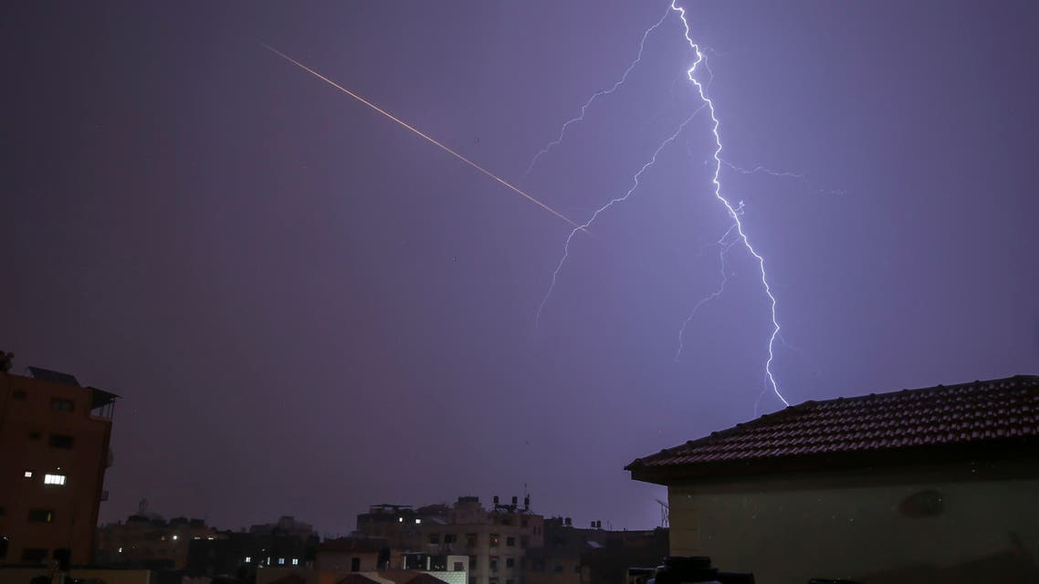 This picture taken from Gaza City shows lightning flashing over buildings as the flair of a rocket launched is seen nearby during a thunderstorm in Gaza city. (AFP)