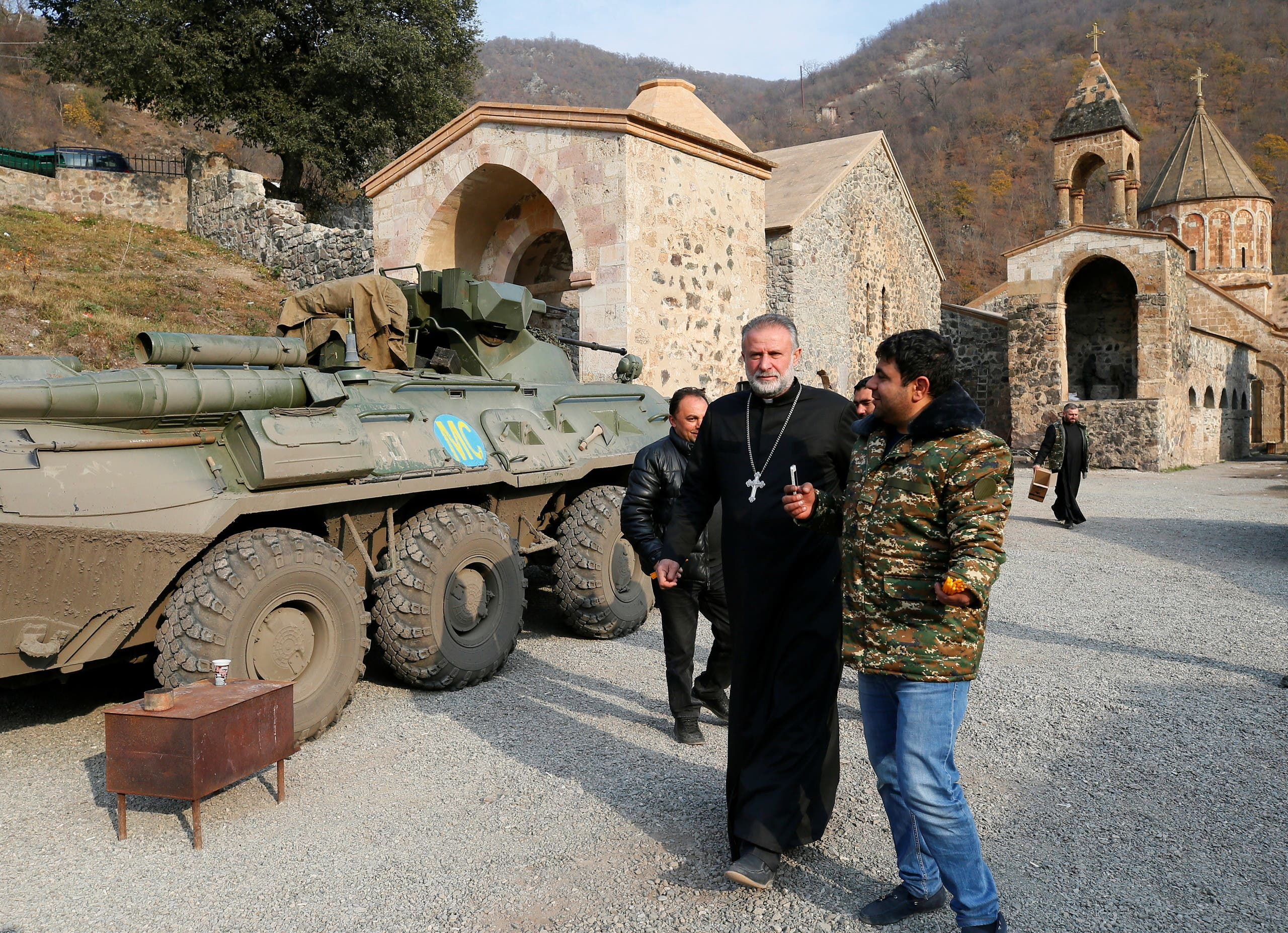 The monastery's abbot Father Hovhannes walks past a military vehicle of the Russian peacekeeping forces at the Dadivank, an Armenian Apostolic Church monastery, located in a territory which is soon to be turned over to Azerbaijan under a peace deal that followed the fighting over the Nagorno-Karabakh region, in the Kalbajar district November 15, 2020. (Reuters)
