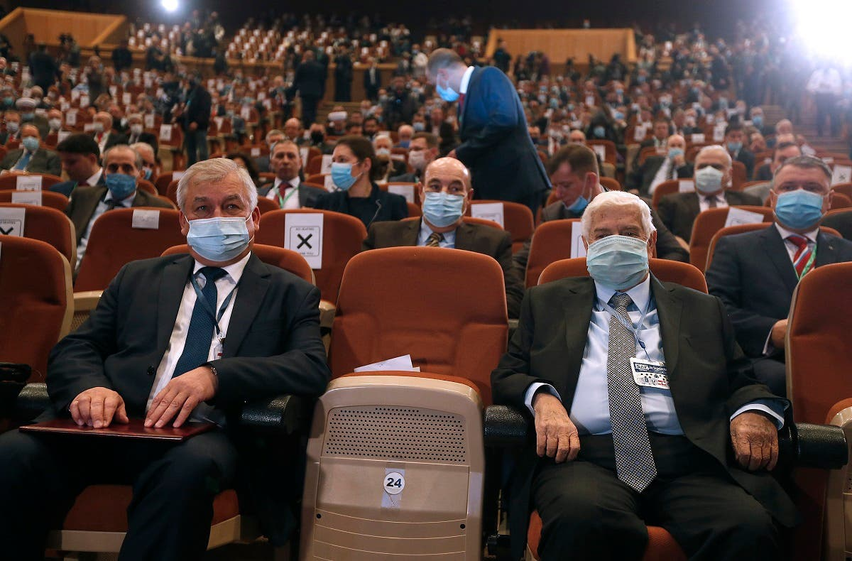 Russia's special envoy on Syria Alexander Lavrentiev (L) sits next to Syrian FM Walid al-Muallem at the opening session of the international conference on the return of refugees held in Damascus on Nov. 11, 2020. (AFP)