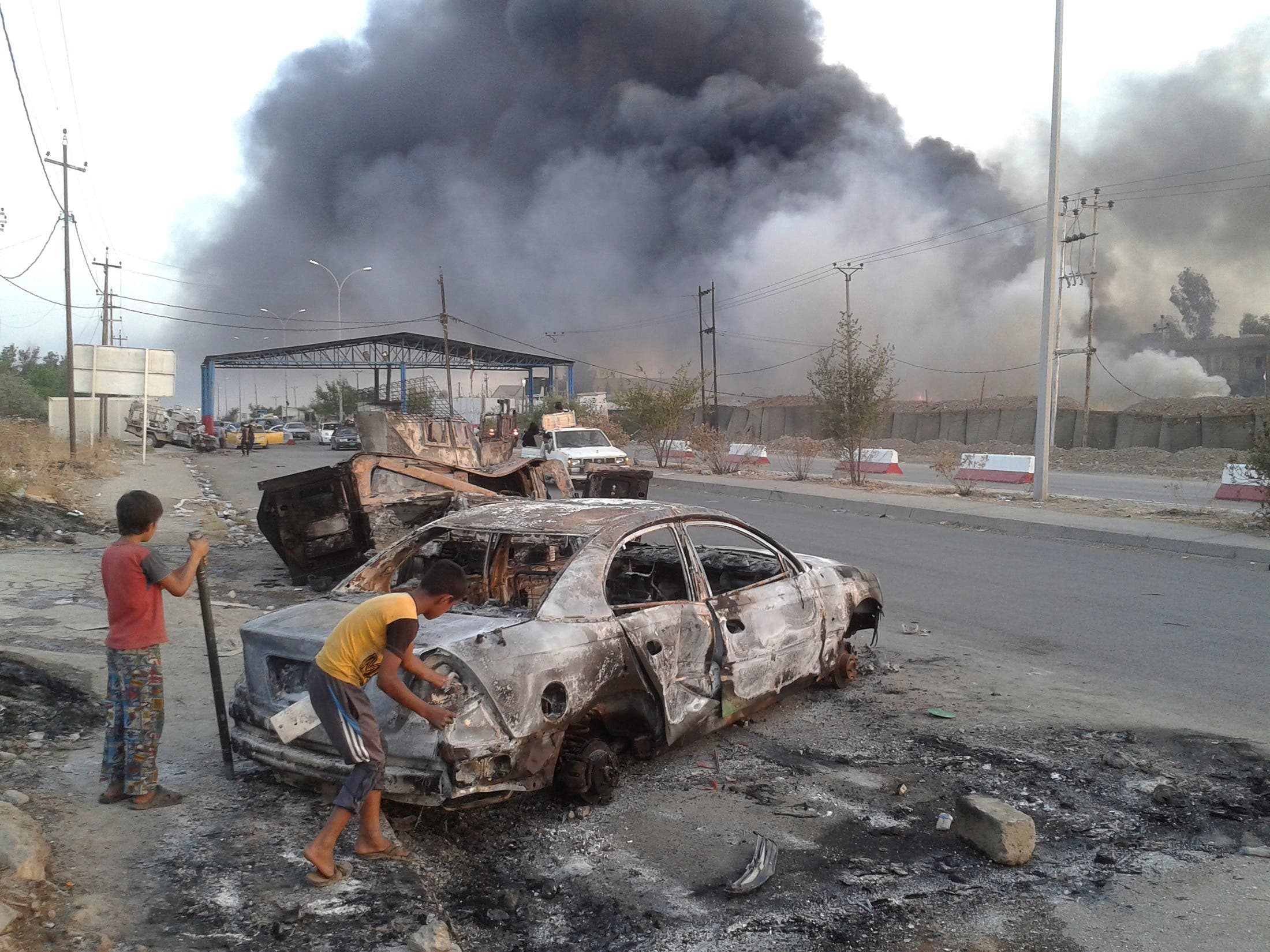 Civilian children stand next to a burnt vehicle during clashes between Iraqi security forces and al Qaeda-linked ISIS in Mosul, Iraq on June 10, 2014. (Reuters)