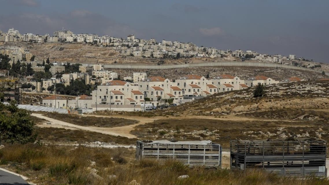 Israel's controversial concrete barrier (C) separating the Jewish settlement of Neve Yaakov (foreground) in the northern part of east Jerusalem and the Palestinian area of al-Ram (background) in the occupied West Bank. (AFP)
