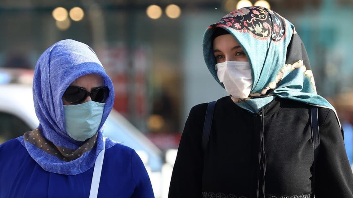 Two Muslim women wear their protective face masks while walking along the street in Ankara on September 18, 2020. (AFP)