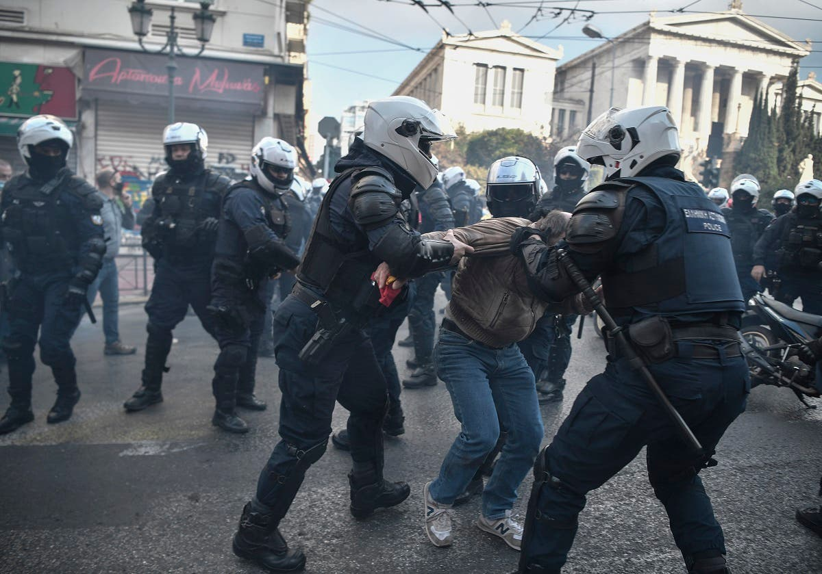 Riot police officers tussle a protester during a demonstration staged by members of the Greek Communist party and leftists to commemorate the 1973 uprising against the military junta, Athens, November 17, 2020. (Louisa Gouliamaki/AFP)