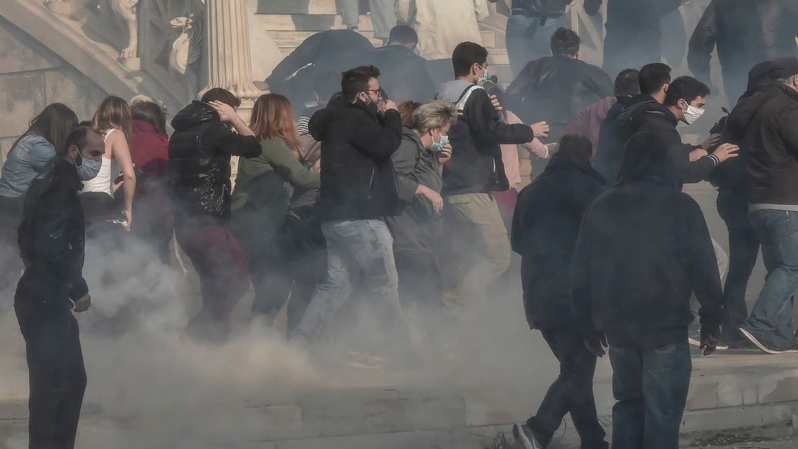 Protesters flee after riot police used tear gas and water cannons against them during a demonstration staged by members of the Greek Communist party and leftists to commemorate the 1973 uprising against the military junta, in central Athens, on November 17, 2020. (Louisa Gouliamaki/AFP)