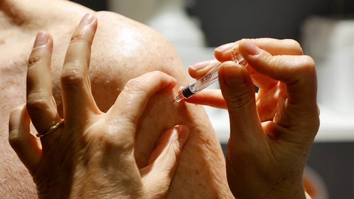 A pharmacist vaccinates a patient against the seasonnal flu at a pharmacy in Paris on october 13, 2020. (AFP)