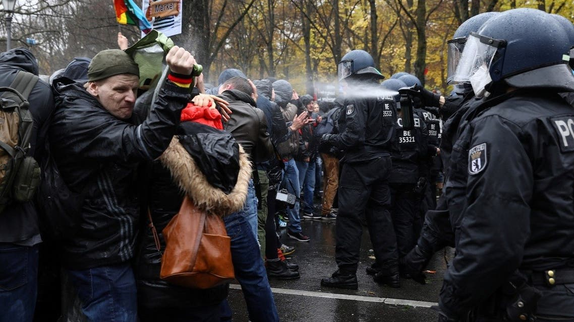 A police officer uses a pepper spray on demonstrators during a protest against the government's coronavirus disease (COVID-19) restrictions, near the Brandenburger Gate in Berlin, November, 18, 2020. (Reuters/Christian Mang)